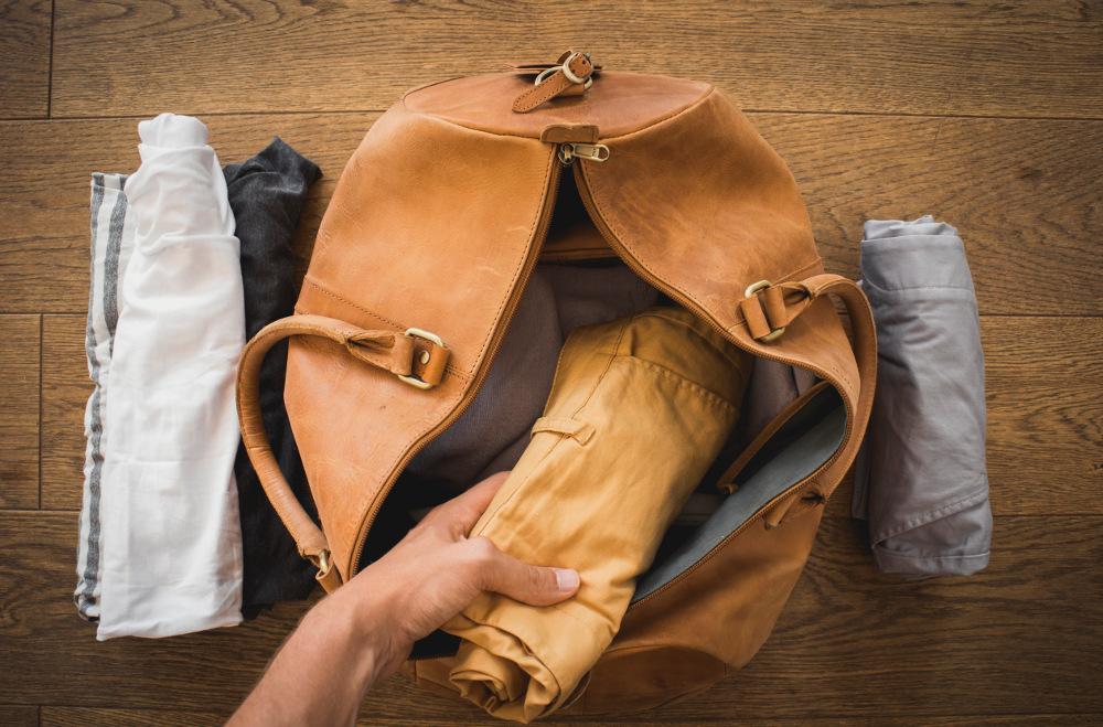 Kleidung einrollen und in der Reisetasche platzieren